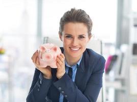 Ritratto di donna d'affari felice mostrando salvadanaio foto