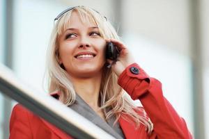 giovane donna che chiama al telefono contro le finestre dell'ufficio foto