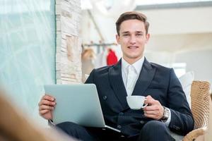 uomo d'affari sorridente in attesa del cliente in sedia e sorridente foto