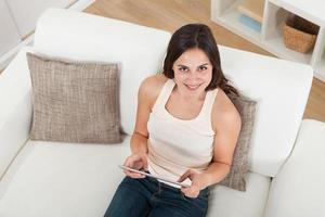giovane donna che per mezzo della compressa digitale sul sofà foto