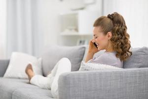 donna che pone sul divano e parlando di telefonia mobile. retrovisore foto