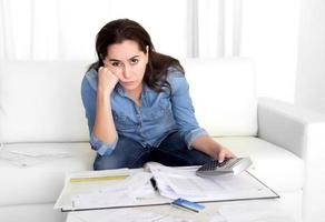 giovane donna a casa nello stress disperato in problemi finanziari foto