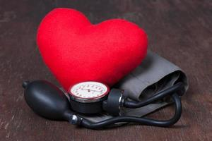 medico, misurare la pressione sanguigna con cuore rosso sul tavolo di legno foto