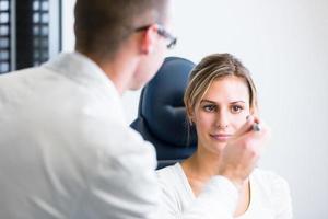 concetto di optometria - bella giovane donna che ha i suoi occhi esaminati foto