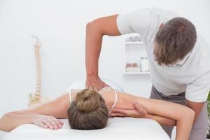 Fisioterapista che fa massaggio alla schiena per il suo paziente foto