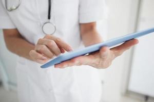 dottor scrolling sul suo tablet foto