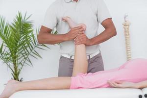 Fisioterapista che fa massaggio alle gambe al suo paziente