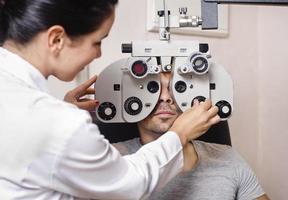 donna optometrista cercando calibrazione phoropter foto