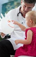 bambina che gioca con il suo pediatra foto