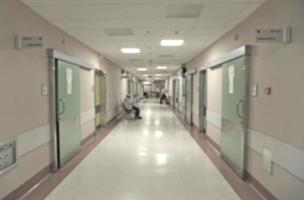corridoio dell'ospedale con porte verdi e pavimenti e pareti beige foto