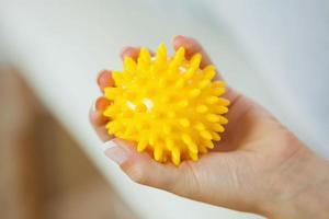 vicino della mano sinistra femminile che tiene la palla gialla di massaggio foto