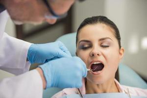 dentista che esamina i denti di un paziente nel dentista foto
