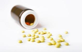 pillole rovesciate gialle da una bottiglia su superficie bianca foto