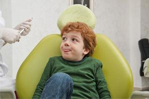 ragazzino carino seduto in poltrona al dentista foto