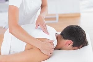 Fisioterapista che fa massaggio alla schiena foto
