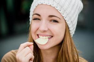 adolescente che mangia patatine foto