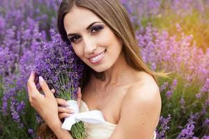 Ritratto di ragazza con il trucco moda al campo di lavanda viola foto