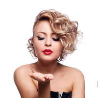 giovane bella femmina bionda che soffia baciata al suo biglietto di S. Valentino foto