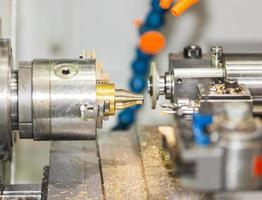 operatore che gira e macina l'autopart di ottone dal tornio di CNC