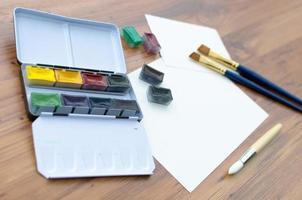 Pinsel mit Wasserfarbe und Papier foto