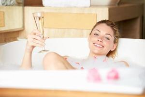 donna che si distende nel bagno bevendo champagne foto
