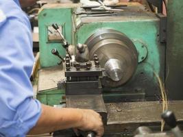 operatore che gira le parti della muffa dal tornio manuale