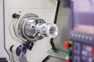 operatore che gira alluminio autopart dal tornio cnc foto