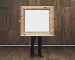 uomo d'affari che tiene lavagna in bianco con la struttura di legno nella r di legno foto