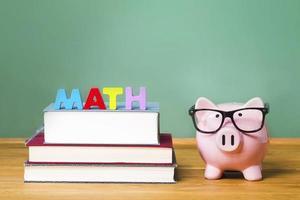 tema di matematica con salvadanaio rosa con lavagna