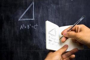 uomo che prende appunti del teorema di matematica sulla lavagna foto