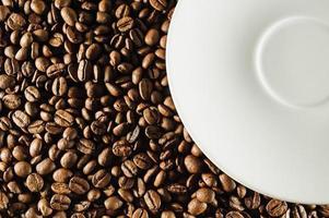 chicchi di caffè e piatto bianco foto