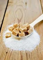 zucchero marrone e zucchero semolato in un cucchiaio sul tavolo foto