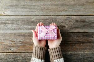 mani femminili che tengono il contenitore di regalo su fondo di legno grigio