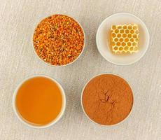 miele, nido d'ape, polline e cannella in ciotole foto