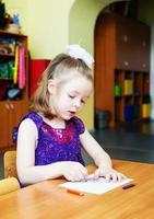 la ragazza seduta al tavolo e disegnando foto