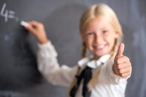 ragazza della scuola scrivendo sulla lavagna foto