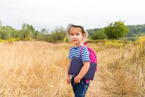 bambina con uno zaino e un libro foto