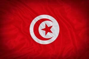 modello di bandiera tunisia sulla trama del tessuto, stile vintage foto