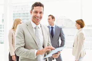 uomo d'affari utilizzando la tavoletta digitale con i colleghi dietro foto