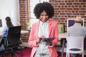 donna che utilizza la tavoletta digitale con i colleghi dietro in ufficio foto