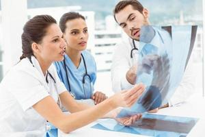 medici maschi e femmine che esaminano raggi x foto