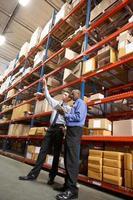 due uomini d'affari con tavoletta digitale in magazzino foto