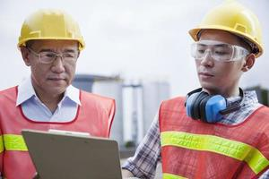 due ingegneri guardando appunti fuori di una fabbrica foto