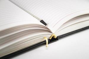 taccuino aperto con il primo piano della penna su una priorità bassa bianca. foto. foto