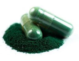 capsula verde della medicina di erbe isolata su fondo bianco foto