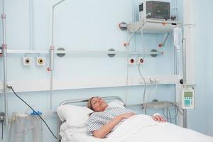 paziente femminile disteso su un letto foto