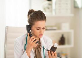 donna del medico con il telefono parlante della bottiglia della medicina foto