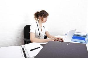 giovane medico femmina che utilizza computer portatile allo scrittorio nella clinica foto