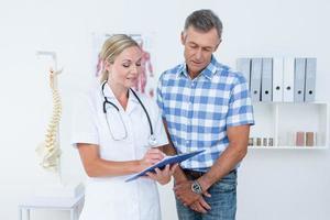medico che mostra appunti al suo paziente foto