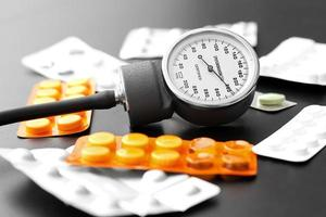 misuratore di pressione sanguigna e pillole sul tavolo foto